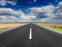 Körning på den tomma asfaltvägen på den idylliska soliga dagen arkivfoto