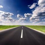 Körning på den tomma asfaltvägen på den idylliska soliga dagen arkivbild