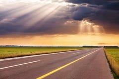 Körning på den tomma huvudvägen in mot solstrålarna Arkivbild