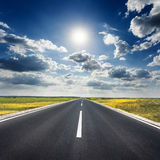 Körning på en tom asfaltväg in mot solen royaltyfri fotografi
