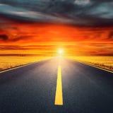 Körning på en tom asfaltväg på solnedgången Arkivbild