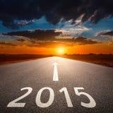 Körning på en tom asfaltväg till kommande 2015 Royaltyfria Bilder