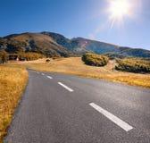 Körning på en tom huvudväg på den härliga soliga dagen royaltyfri bild