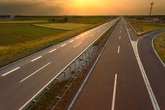 Körning på en tom motorway på solnedgången arkivbild