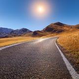 Körning på en tom väg i bergområde Arkivbild