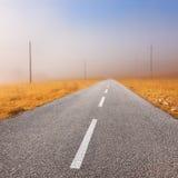 Körning på en tom väg in mot dimman Arkivbilder