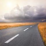 Körning på en tom väg in mot stormen Royaltyfria Bilder