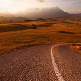 Körning på en tom väg på solnedgången Arkivfoto