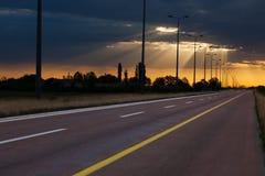 Körning på en tom väg till härlig soluppgång med Arkivfoton