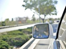 Körning på Kalifornien vägar nära kusten med spegeln för bakre sikt från bilen i ram Arkivfoton