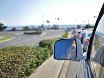 Körning på Kalifornien vägar nära kusten med spegeln för bakre sikt från bilen i ram Royaltyfri Bild