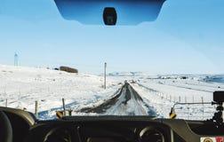 Körning på landsvägen i vinter Se till och med bilframdelvindrutan, täckte gör klar den fryste vägen med snö och blå himmel in I Arkivfoton