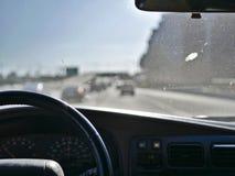 Körning på Los Angeles Kalifornien motorvägar i mild trafik med en smutsig vindruta royaltyfri foto
