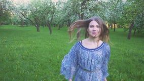 Körningar för ung kvinna i en äpplefruktträdgård blommar på våren vit Stående av en härlig flicka i aftonfrukten stock video