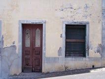 Körningen ner tomt övergett hus med att smula gula målade väggar bommade för stängda slutare och en bruten trädörr royaltyfri foto