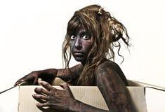 Körper gemalte Frau, die im Kasten sitzt Lizenzfreie Stockbilder