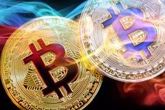 Körperliche Version neuen virtuellen Geldes Bitcoin mit buntem Rauche stockbild