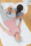Körperlicher Therapeut, der das Bein der älteren Frau überprüft Lizenzfreies Stockfoto