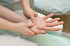 Körperlicher Therapeut, der Hände massiert Stockbild