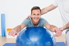 Körperlicher Therapeut, der jungen Mann mit Yogaball unterstützt Lizenzfreie Stockfotos