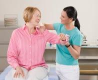 Körperlicher Therapeut, der womans Schulter überprüft Stockfotos