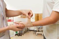 Körperlicher Therapeut hilft dem Patienten der Frau, der eine Handgelenkklammer trägt Lizenzfreie Stockfotos
