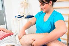 Körperlicher Therapeut massiert männliches Bein Lizenzfreie Stockfotografie