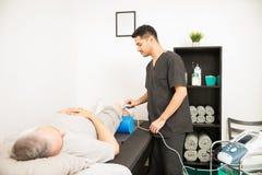 Körperlicher Therapeut Using Ultrasound Probe auf geduldigem Knie lizenzfreie stockfotos