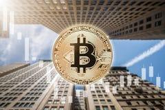 Körperliches Münzensymbol Bitcoin mit Abwärtstendenzkerzenständerpreistafel und Wolkenkratzerhintergrund Stockbilder