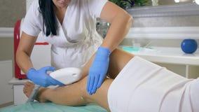 Körperpflege, Kosmetiker Doctor, das Laser-Haarabbau auf weibliche geduldige Füße in der Kliniknahaufnahme, Apparat für durchführ stock video footage
