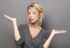 Körpersprachkonzept für zweifelhafte blonde Frau 20s Stockfotos