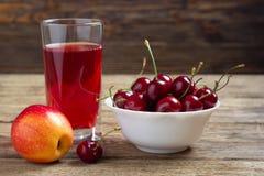 Körsbär, äpple och ett exponeringsglas av fruktsaft royaltyfria foton
