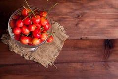 Körsbär i en bunke på trätabellen Arkivfoton