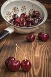 Körsbär i en durkslag Arkivfoto