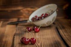 Körsbär i en durkslag Arkivbilder