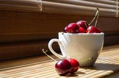 Körsbär i en vit kopp på en träbakgrund arkivbild