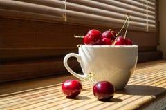 Körsbär i en vit kopp på en träbakgrund royaltyfria foton