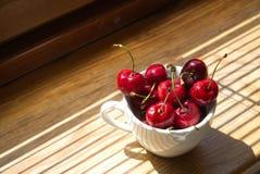Körsbär i en vit kopp på en träbakgrund royaltyfri bild
