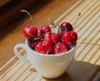 Körsbär i en vit kopp på en träbakgrund royaltyfria bilder