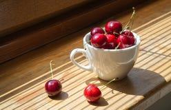 Körsbär i en vit kopp på en träbakgrund arkivbilder