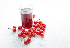 Körsbär i ett exponeringsglas på en trätabell, nya drinkar, Royaltyfria Foton