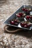 Körsbär i ett muffintenn Royaltyfria Bilder