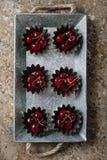 Körsbär i ett muffintenn Arkivfoton
