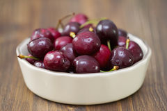 Körsbär i maträtt på mörker Arkivfoton