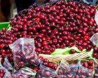 Körsbär i påsar på marknaden Arkivbild