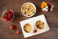 Körsbär jordgubbesmulpajefterrätt i vita bunkar Körsbär jordgubbar, blommor bakom Mörk wood bakgrund, bästa sikt arkivfoto