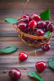 Körsbär med sidor i en korg på träbakgrund Arkivfoto