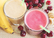 Körsbär- och banansmoothie med nya körsbär och bananer Cherry Milkshake bananmilkshake nya greenleaves Arkivfoto