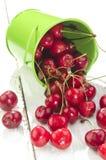 Körsbär och en grön hink Royaltyfri Foto