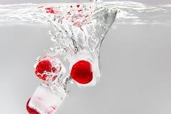 Körsbär och hallon som faller in i vattenmakro Lemonadbegrepp arkivbild